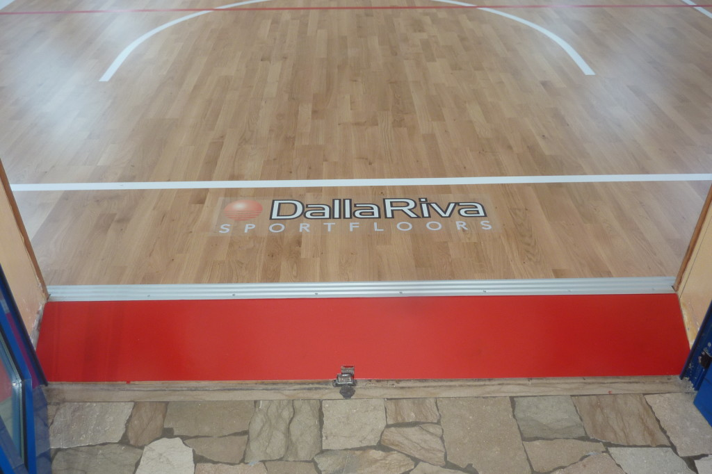 A connecting ramp between the new sports floor and a door, beautiful and functional contrast between the oak and the red