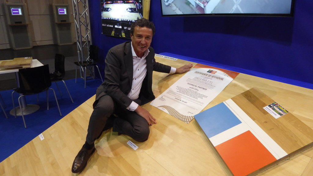 Luigino Dalla Riva proudly shows the document certifying that their company is an official partner Fiba
