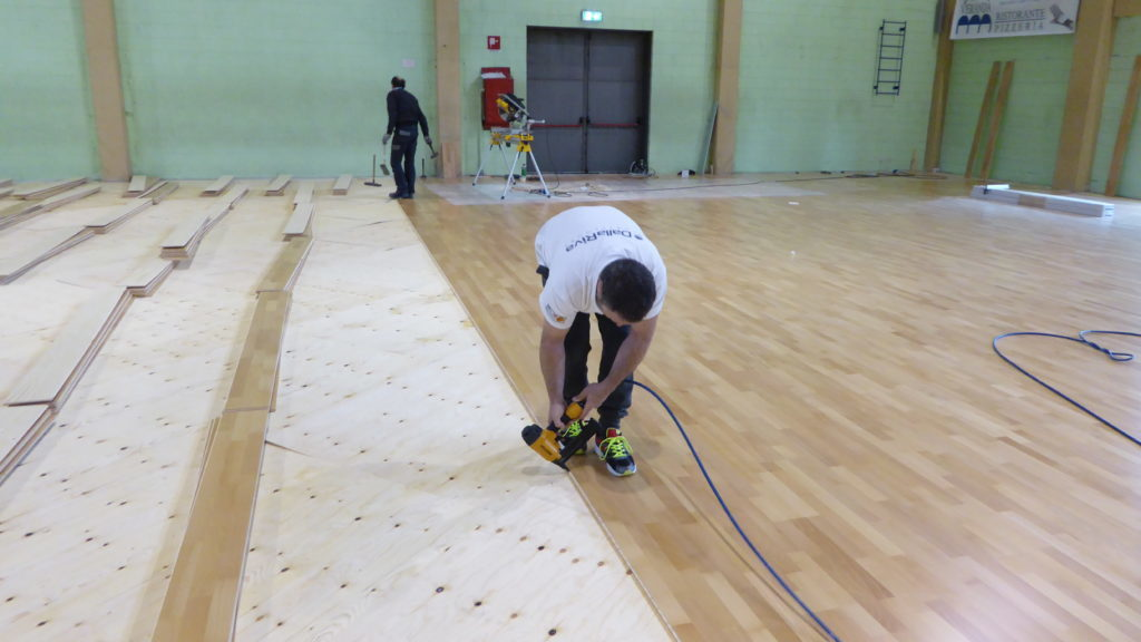 Technicians DR during the installation phase of the new sports parquet at PalaErba