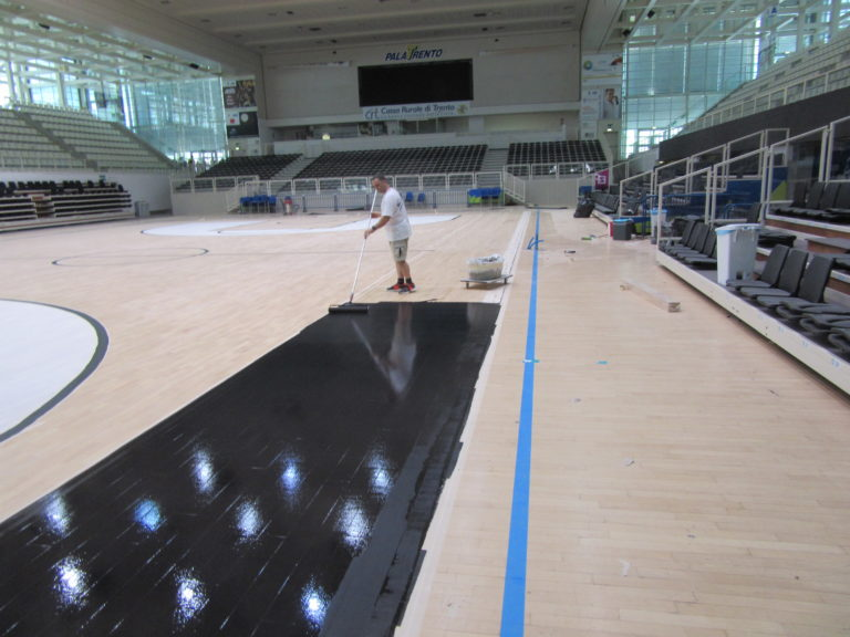 Customization phases with the black paint of the new PalaTrento sports parquet