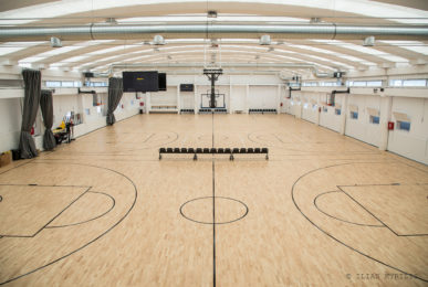 Sports parquet Dalla Riva Sportfloors model Compact 45 with FIBA certification for the creation of a white longitudinal field at competitive levels and three black transversal training fields.