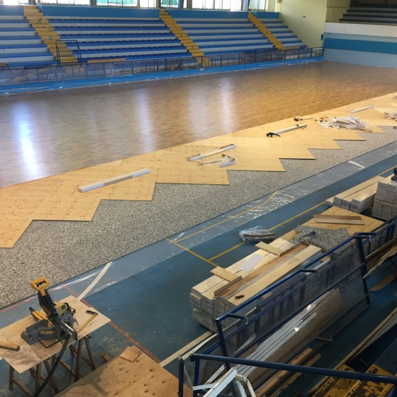 In one photo, vapor barrier, elastic mat, plywood and oak sports parquet